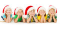Christmas kids smiling in red hat santa group of five children lying down over white background Royalty Free Stock Image