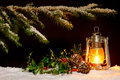 Christmas lantern scene an oil filled burning bright with snow covered tree holly and ivy lit up by the glow of the lamp Stock Photo