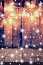 Christmas light, snow on wooden background and wooden table with Royalty Free Stock Photo