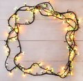 Christmas lights background. Holiday glowing garland on light wo Royalty Free Stock Photo