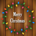 Christmas lights frame wreath made of colorful on a wooden background Royalty Free Stock Images