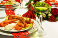 Christmas lobster table and white wine on a festive with red folded napkins and red ribbon trims Stock Photography