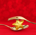 Christmas menu golden cutlery with ornament on red background Stock Photos