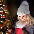 Christmas miracle smiling blonde girl with knitted hat with gift box opening over lights of tree Stock Images