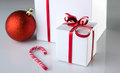Christmas modern still white gift boxes with red bright bow red ball and candycane on light grey background Royalty Free Stock Image