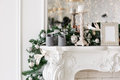 Christmas morning. classic luxury apartments with a white fireplace, decorated tree, bright sofa, large windows Royalty Free Stock Photo