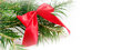 Christmas or New Year Background with green branch, vibrant red bow Royalty Free Stock Photo