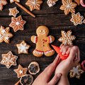 Woman decorating Christmas gingerbread man cookie