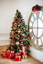 Christmas and New Year decorated white interior room with presents and New year tree with red decor ball. Grey sofa and