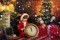 Christmas or New Year time. Cute child in santa claus hat holding red alarm clock with thumb up. Twelve O`clock midnight Royalty Free Stock Photo