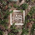 Christmas and New Year Typographical on wooden background with fir branches, frame of paper card note, pine cones and snowflakes Royalty Free Stock Photo