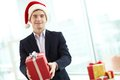 Christmas in office image of happy businessman santa cap with giftbox looking at camera Stock Photo