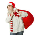 Christmas old man with beard in red hat carrying santa claus bag over white background Royalty Free Stock Photography