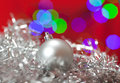 Christmas ornament close up of a silver in shiny tinsel with lights in the background Royalty Free Stock Images
