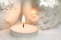 Christmas ornaments and candle silver a burning in the snow Stock Image