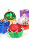 Christmas ornaments in cupcake liners with gifts Royalty Free Stock Photography