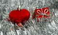 Christmas ornaments on silver tinsel heart and red gift box placed Royalty Free Stock Photo