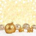 Christmas ornaments in snow with twinkling gold background Royalty Free Stock Photo