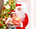 Christmas party for children santa claus with granddaughter sitting near tree cute girl opening gift box glowing lights magic Royalty Free Stock Images