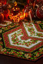 Christmas patchwork napkin, christmas candle holder with flaming candle inside and christmas decorations blurred on back view Royalty Free Stock Photo