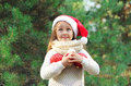 Christmas and people concept - little girl child in santa red hat with balls Royalty Free Stock Photo