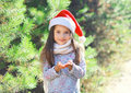 Christmas and people concept - little girl child in santa red hat blowing snow in hands Royalty Free Stock Photo
