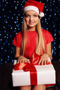 Christmas photo of cute little blond girl in santa hat and red dress holding a gift - box on the backgroud of holiday shining ligh Royalty Free Stock Photo