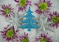 Christmas photography picture of glitter tree and star decorations with purple green flowers in snow in the background Royalty Free Stock Photo