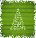 Christmas pine and border made of snowflakes on green wooden ba Royalty Free Stock Photo