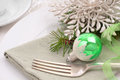 Christmas place setting on table with vintage ornament and copyspace horizontal closeup of a a green silver glittered snowflake Stock Photos