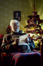 Christmas portrait of father sitting in armchair reading letters Stock Image