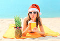 Christmas portrait pretty young woman in red santa hat with pineapple drinking from cup fresh fruit juice lying on beach over sea Royalty Free Stock Photo