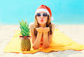 Christmas portrait pretty young woman in red santa hat with pineapple sends air kiss lying on beach over blue sea Royalty Free Stock Photo