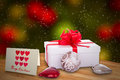 Christmas present gift box with red ribbon card and baubles with sparkling lights in the background Stock Photo