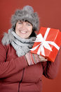 Christmas present happily smiling woman with a over red background Stock Image