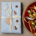 Christmas present and ornaments high angle closeup of a tissue wrapped on a burlap surface square format Royalty Free Stock Images