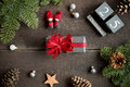 Christmas present with red ribbon, christmas calendar, pine branches, cone and xmas decorations. Royalty Free Stock Photo