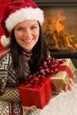 Christmas present woman Santa hat home fireplace Stock Image