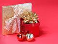 Christmas presents gift boxes with gold bow and shiny balls over red background Stock Image