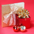 Christmas presents gift boxes with gold bow and shiny balls over red background Stock Photo