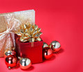 Christmas presents gift boxes with gold bow and shiny balls over red background Royalty Free Stock Images
