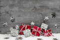 Christmas presents in red and silver on wooden grey background.