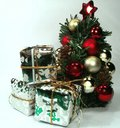 Christmas presents stacked togeather near tree with red and golden decoration balls and red star on top of it Royalty Free Stock Photography