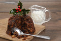 Christmas pudding on a cutting board with cream Royalty Free Stock Photo