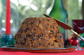 Christmas pudding homemade on a plate with red and green festive background Stock Image