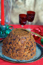 Christmas pudding homemade traditional on a plate with red candle and port glasses in the background Royalty Free Stock Photography