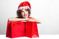 Christmas purchases beautiful woman in santa claus red hat with red packages Royalty Free Stock Photos
