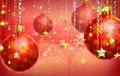 Christmas red abstract background with several decorations hanging down christmass at the foreground and a few balls out of focus Stock Image