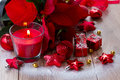 Christmas red candle with decorations burning on wooden table Stock Photos