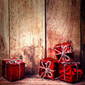 Christmas red gift boxes with ribbon on rustic wood board with c copy space for greeting text festive decoration over wooden Royalty Free Stock Image
